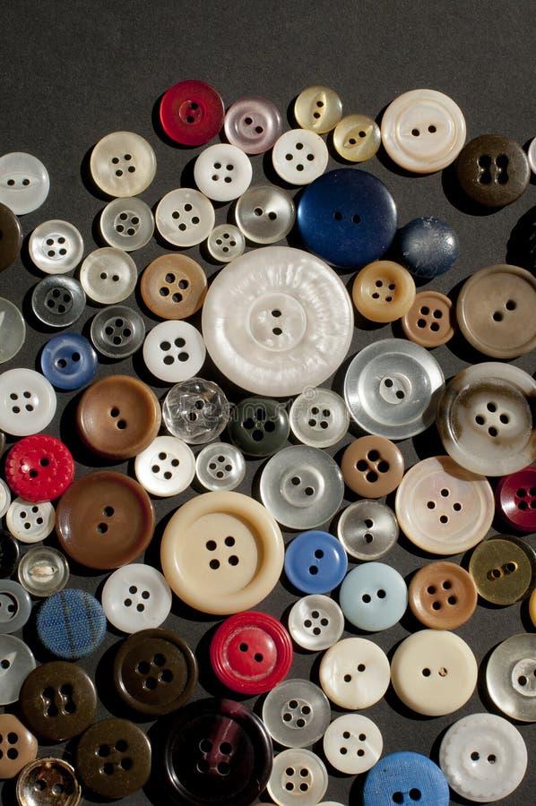 Rangée colorée de grands et petits boutons dispersés image libre de droits