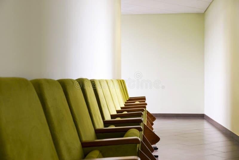 Rangée d'amphithéâtre vert posant les chaises molles avec des blocs - notes placés le long du mur dans le couloir Affaires ou évé photos stock