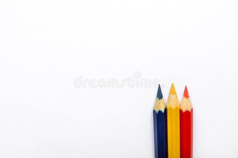 Rangée de bleu jaune rouge de trois crayons multicolores au fond et au dessus sur le fond de livre blanc Conception graphique de  photo stock