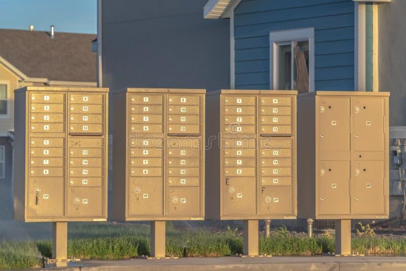Rangée de boîtes aux lettres avec des numéros et des compartiments à côté d'une route par jour ensoleillé photo stock