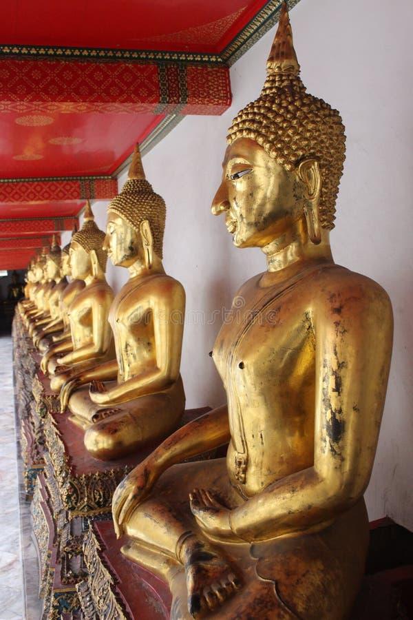 Rangée de Buddhas d'or photo stock