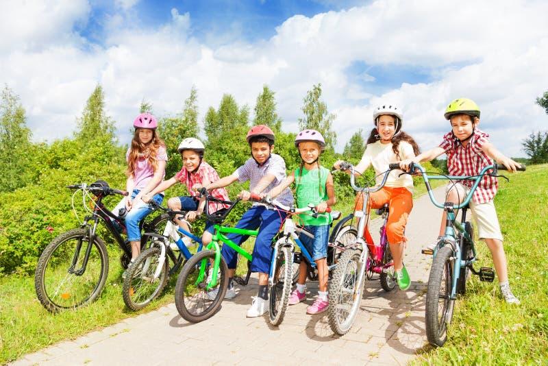 Rangée de diversité d'enfants dans les casques et des vélos photos stock
