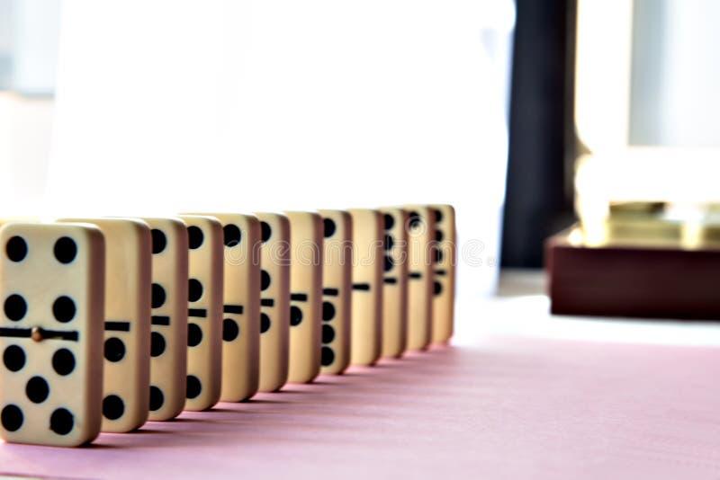 Rangée de domino sur le fond rose photographie stock libre de droits