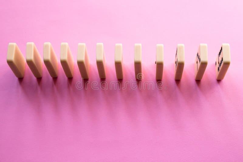 Rangée de domino sur le fond rose Configuration plate photos libres de droits