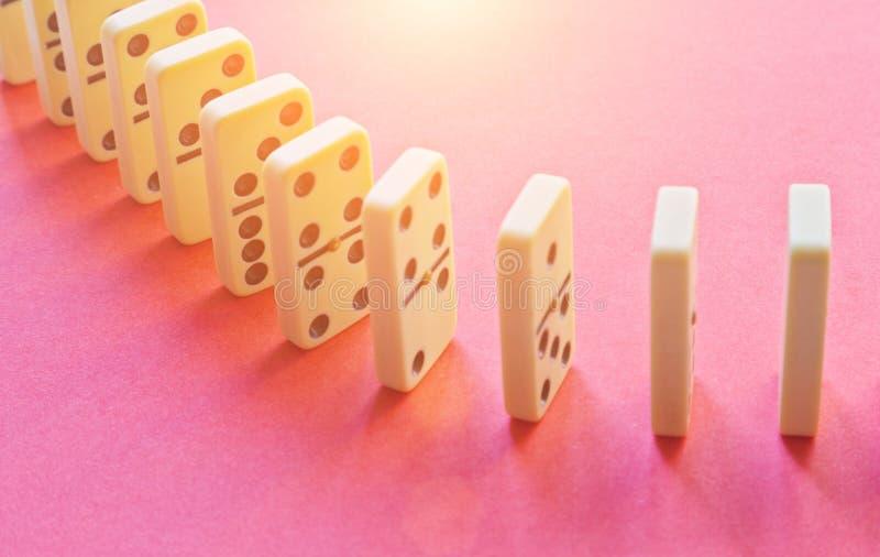 Rangée de domino sur le rose photos stock