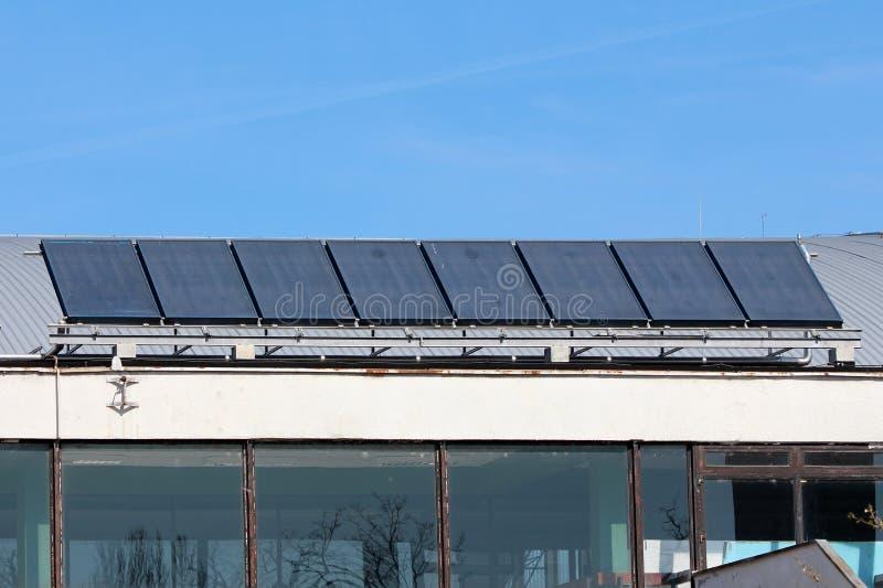 Rangée de grands panneaux solaires foncés de chauffage d'eau montés sur le vieux toit en métal de la salle de gymnastique locale photo libre de droits