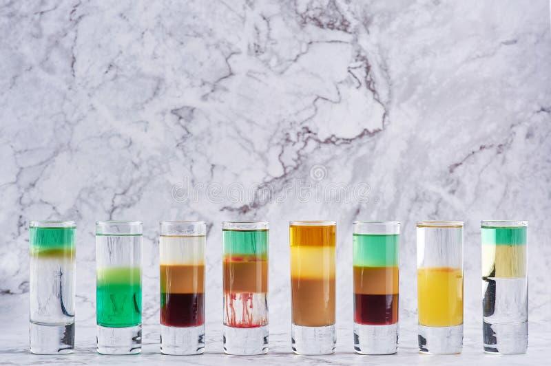 Rangée de huit cocktails différents de tir d'alcool au contexte de marbre photos libres de droits