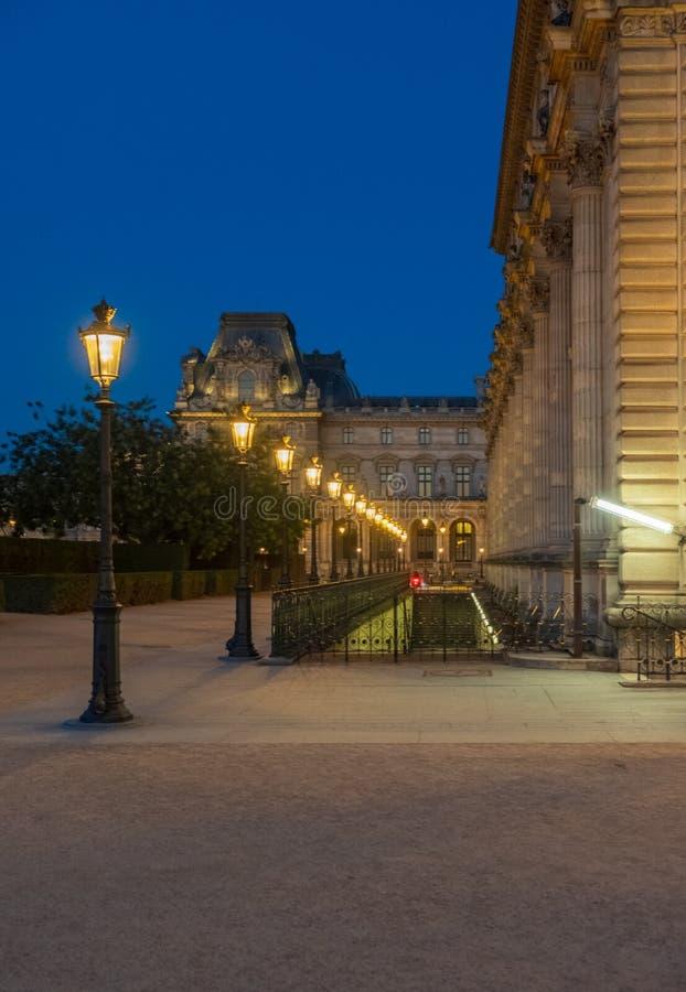 Rangée de Lampost en dehors du musée de Louvre à Paris par nuit image stock