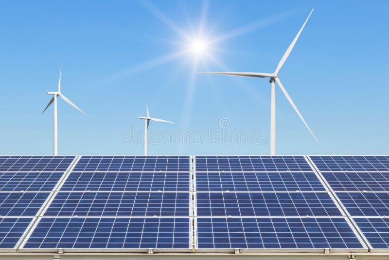 Rangée de rangées de panneaux solaires de silicium polycristallin et de turbines de vent produisant de l'électricité dans la stat images libres de droits