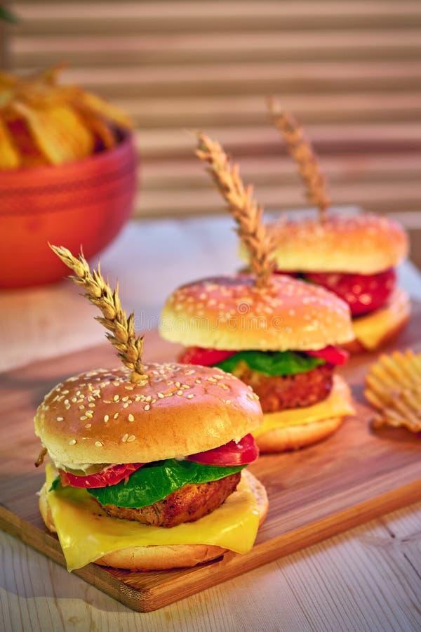 Rangée de trois hamburgers appétissants à la mode sur le conseil en bois dans le restaurant Foyer sélectif, perspective Aliments  photo stock