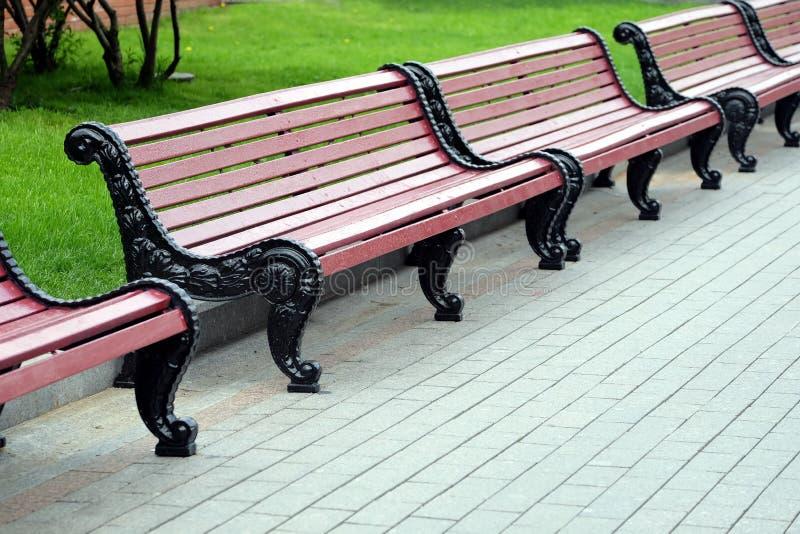 Rangée des bancs en bois bruns vides en parc de ville photographie stock