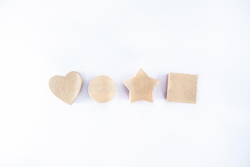 Rangée des boîte-cadeau de papier de métier Recycled dans la forme de l'étoile, du coeur, de la place et du cercle rond sur le fo image libre de droits
