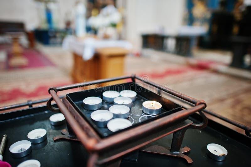 Rangée des bougies brûlantes de cercle sur un support à l'église photos libres de droits