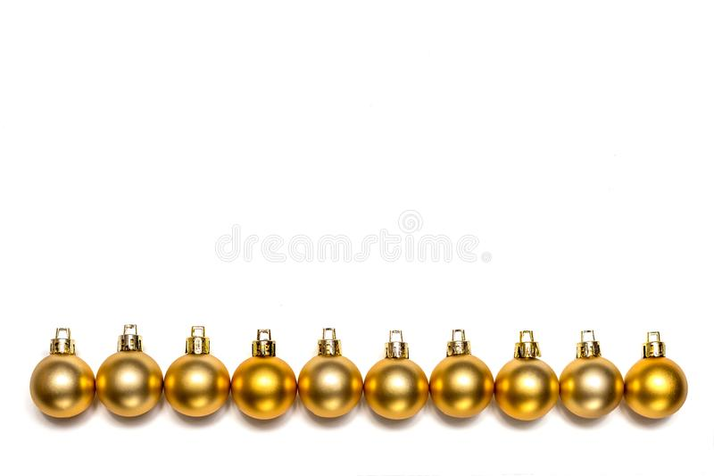 Rangée des boules de nouvelle année et de Noël d'or d'isolement photos stock