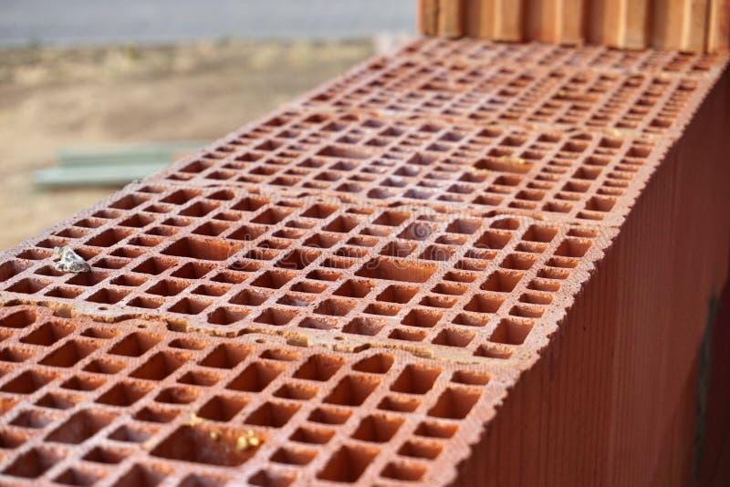 Rangée des briques rouges avec les trous sous forme de nid d'abeilles sur le chantier de construction photographie stock libre de droits