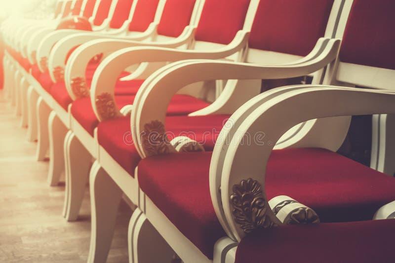 Rangée des chaises rouges de vintage dans l'opéra ou le hall de cinéma ou d'événement, la perspective et le foyer sélectif photographie stock libre de droits