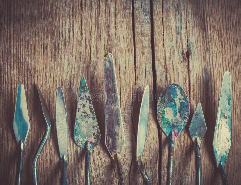 Rangée des couteaux de palette d'artiste sur le vieux contexte rustique en bois photographie stock