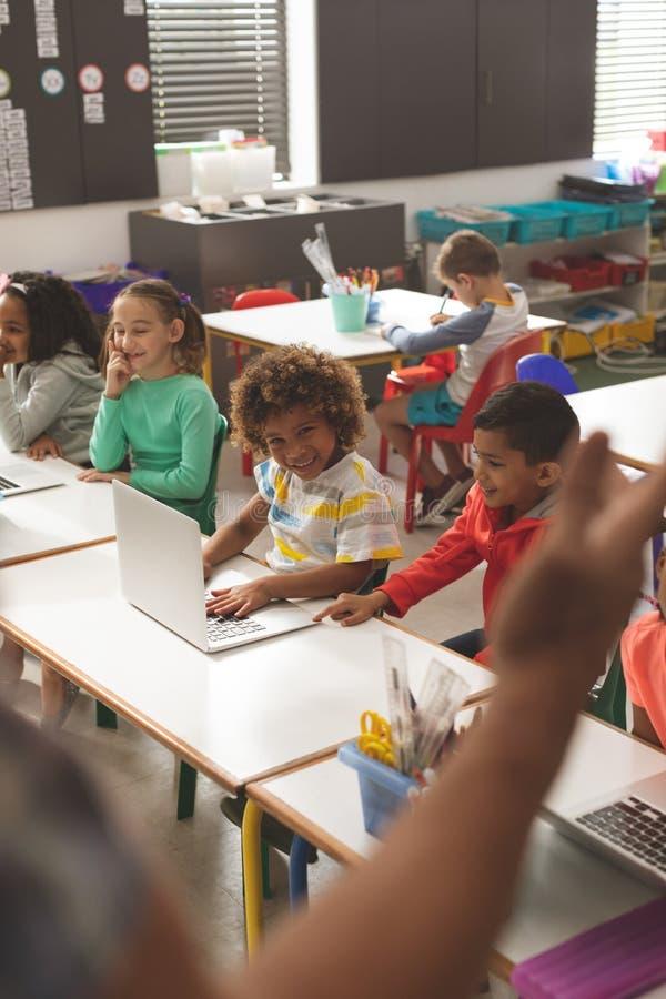 Rangée des enfants d'école smilling tandis qu'ils écoutent leur professeur images stock