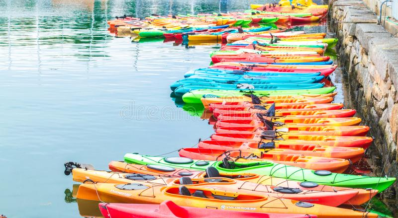 Rangée des kayaks colorés pour le loyer dans l'eau images stock