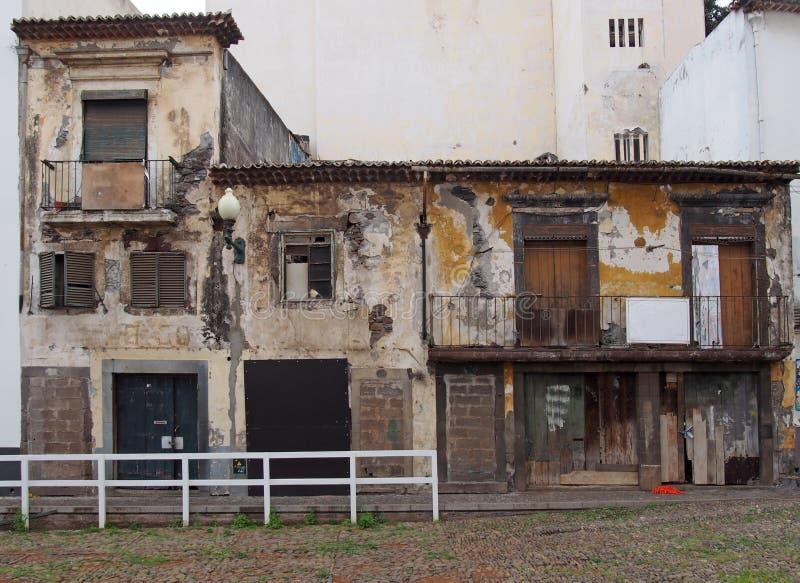 Rangée des maisons et des biens commerciaux abandonnés abandonnés sur une rue avec les portes et les murs hauts embarqués de fenê images stock