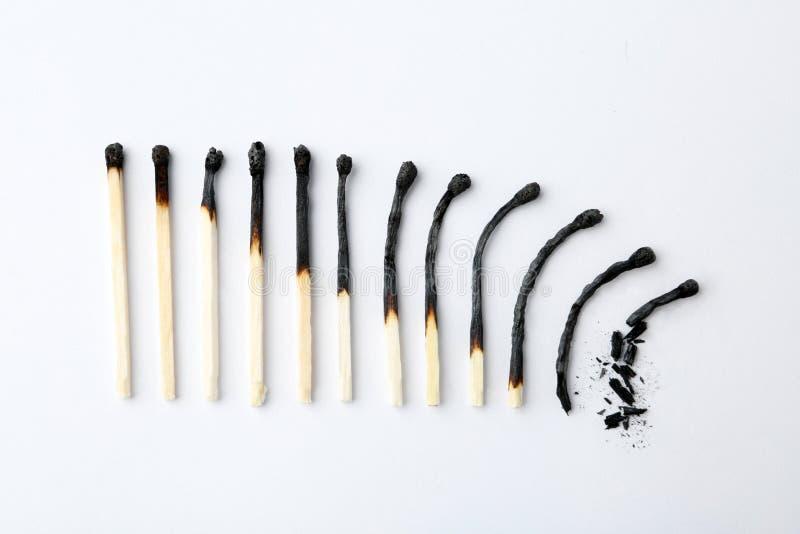 Rangée des matchs brûlés sur le fond blanc Concept de phases de vie humaine photographie stock