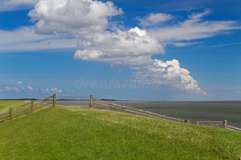 Rangée des nuages au-dessus de la digue photo stock