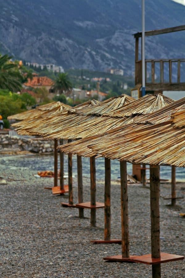 Rangée des parasols de paille sur la plage vide dans Monténégro image libre de droits
