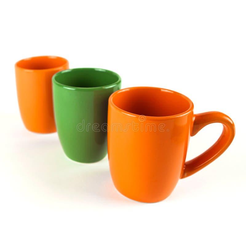Rangée des tasses de café saisonnières dans orange et vert sur le fond blanc photographie stock
