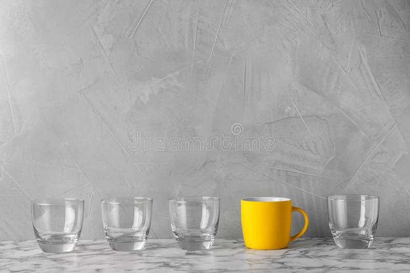 Rangée des verres avec la tasse lumineuse sur la table photographie stock libre de droits