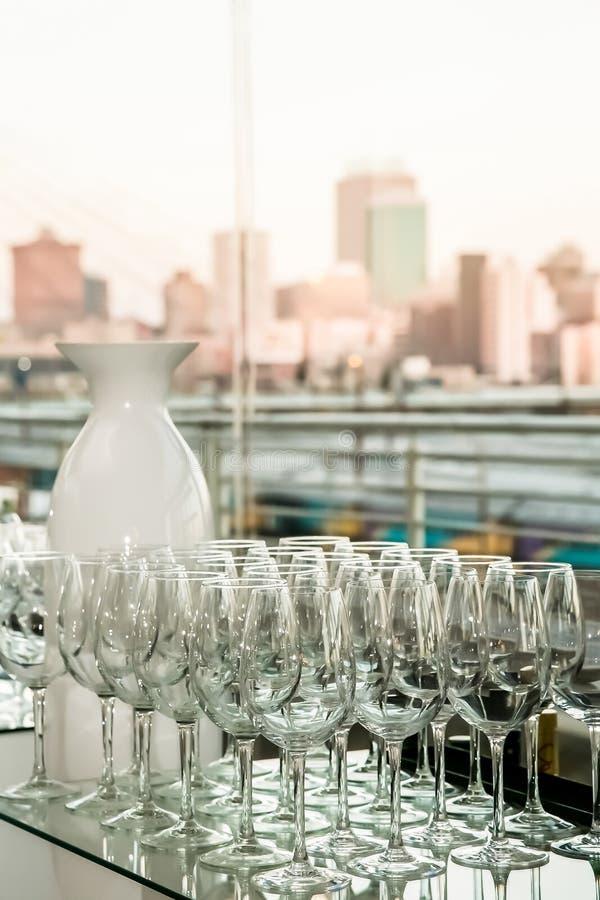 Rangée des verres de vin vides sur un plan de travail en verre images stock