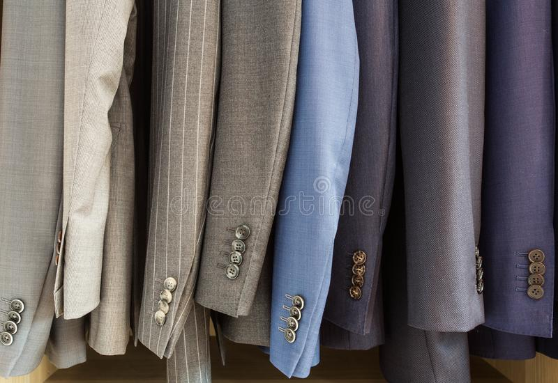 Rangée des vestes de costume des hommes sur des cintres image libre de droits