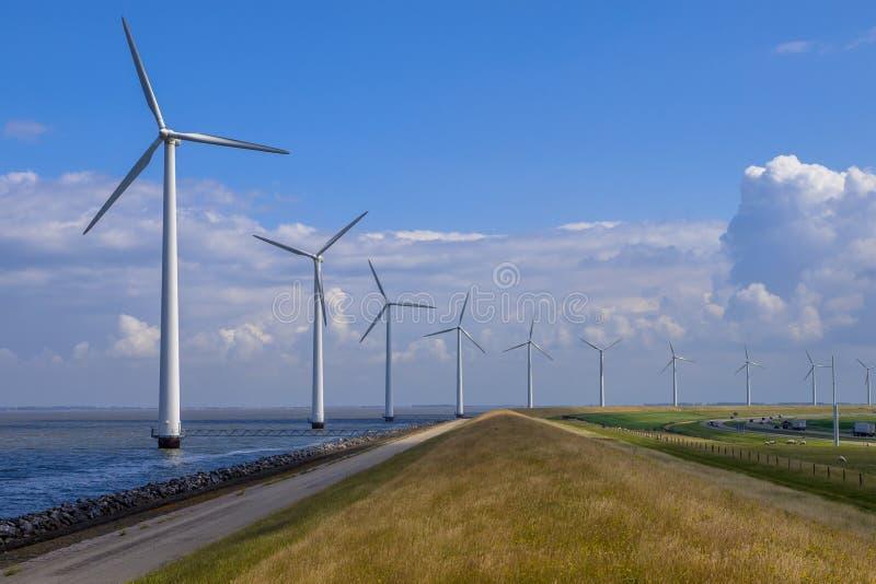Rangée des windturbines le long d'une digue images stock