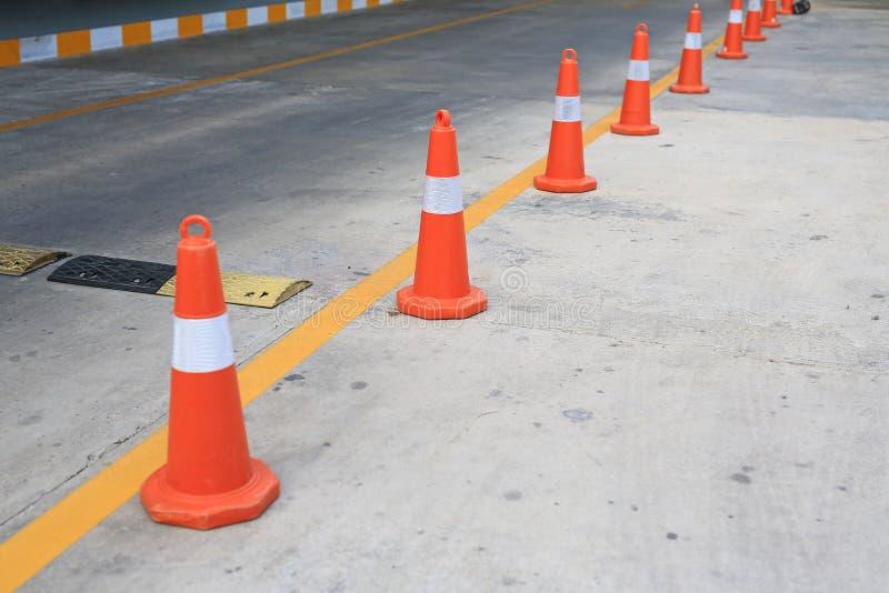 Rangée du cône en caoutchouc orange du trafic placé dans la route photos stock