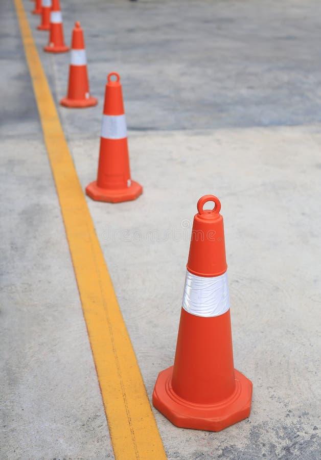 Rangée du cône en caoutchouc orange du trafic placé dans la route images stock