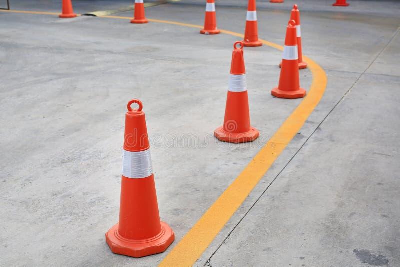 Rangée du cône en caoutchouc orange du trafic placé dans la route photographie stock libre de droits
