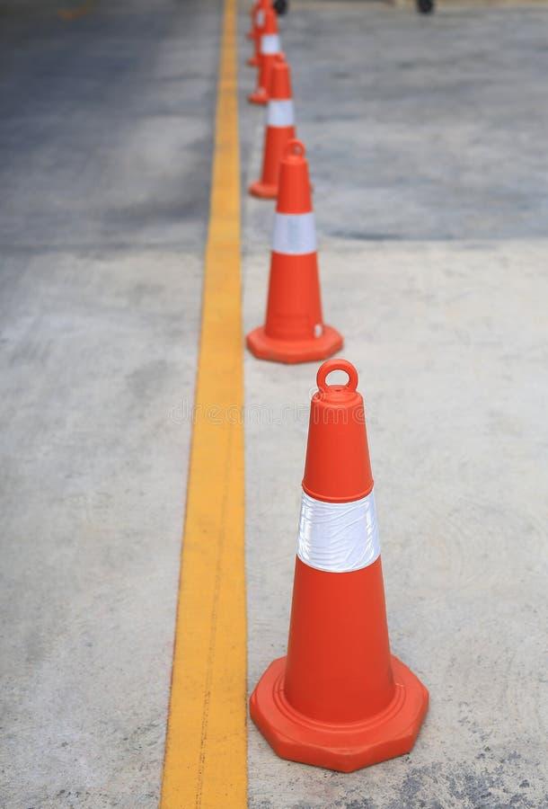 Rangée du cône en caoutchouc orange du trafic placé dans la route photo stock