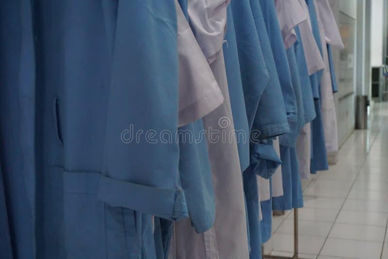 Rangée du manteau blanc et bleu de laboratoire images stock