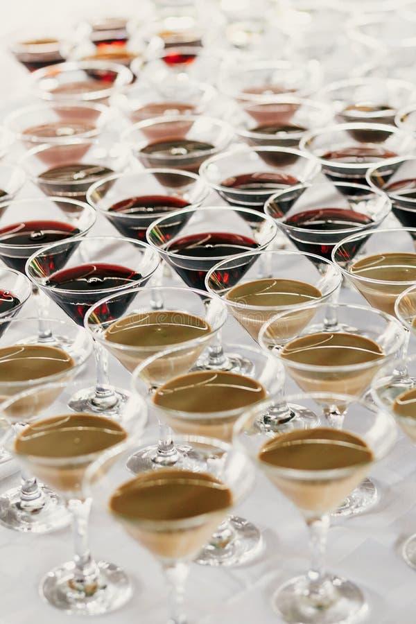 Rangées de Martini sur la table à la réception de mariage Cocktails et martini rouge et blanc en verres à la barre d'alcool au ma photographie stock libre de droits