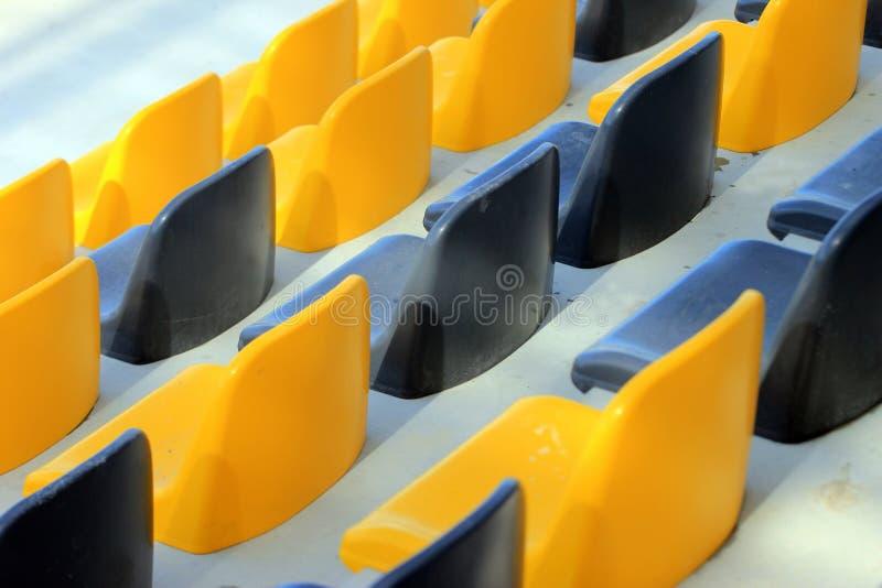 Rangées de vieux sièges noirs et jaunes en plastique sales à un stade photos libres de droits