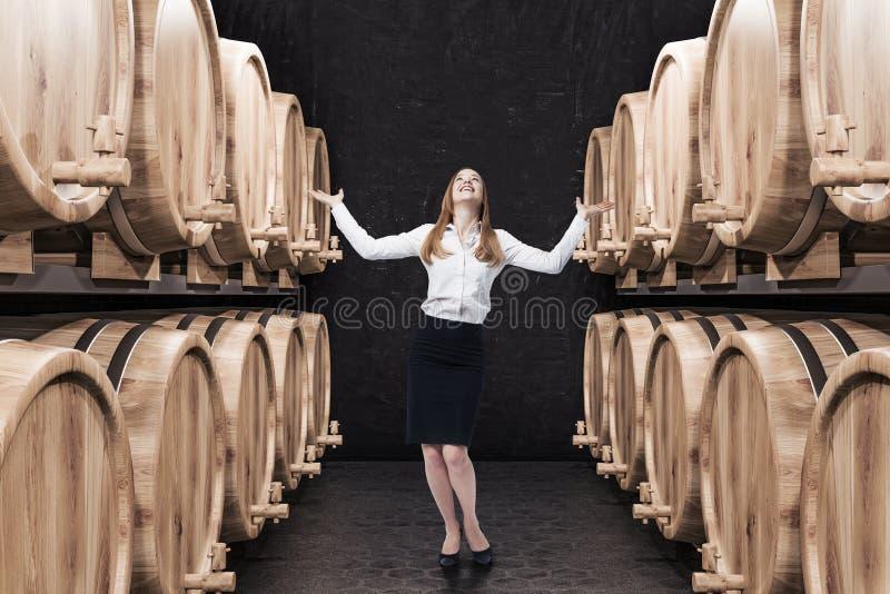 Rangées des barillets de vin ou de bière dans la cave, femme images stock