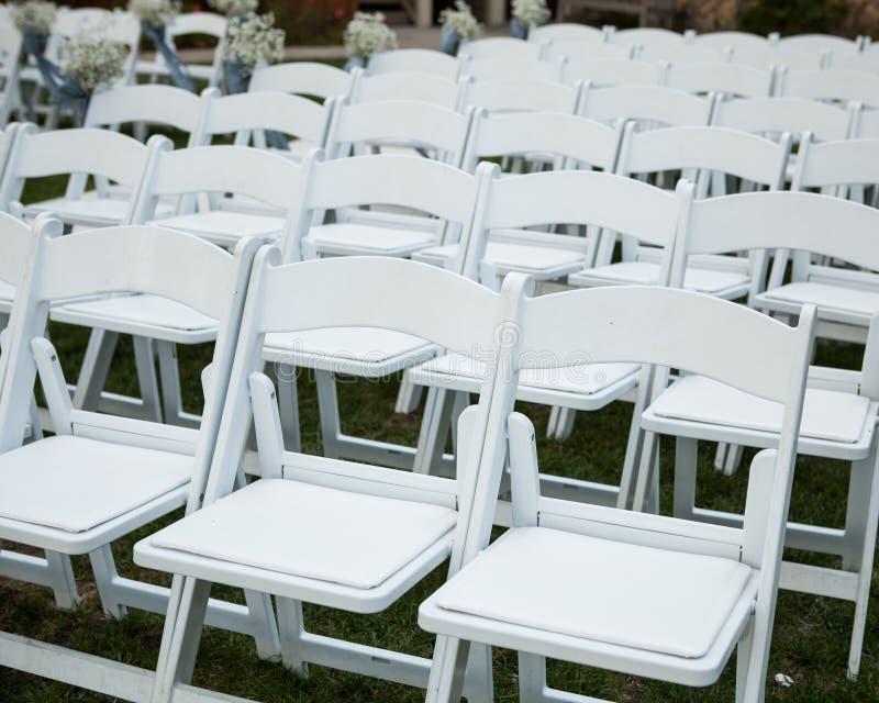 Rangées des chaises blanches vides sur une pelouse verte photographie stock libre de droits