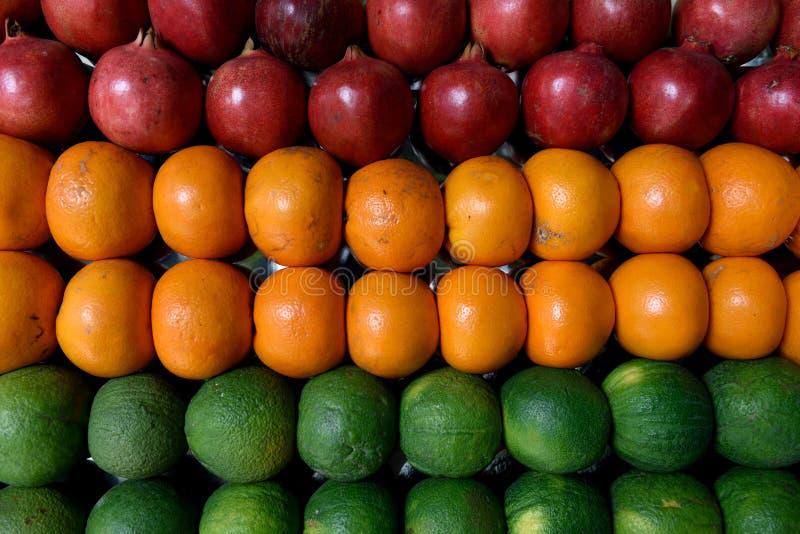 Rangées des fruits frais, des grenades, des oranges et des chaux colorés moissonnés frais photos stock