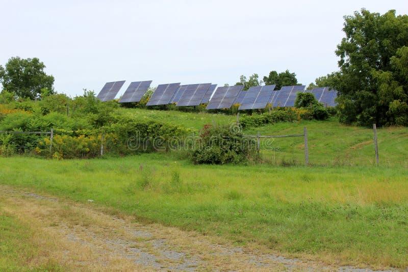 Rangées des panneaux solaires dans le pré ouvert sur la route de campagne rurale photo libre de droits