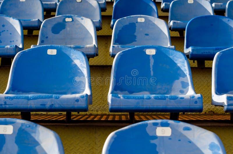 Rangées des sièges humides identiques dans les grandins vides de stade image stock