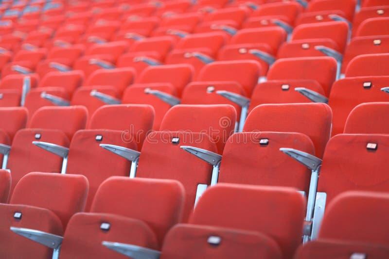 Rangées des sièges numérotés rouges avec des accoudoirs images stock