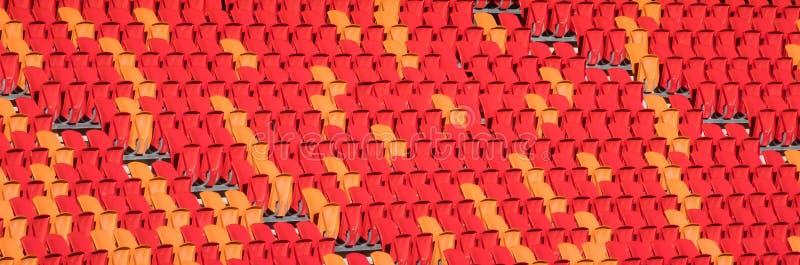 Rangées des sièges rouges et oranges vides de stade photos stock