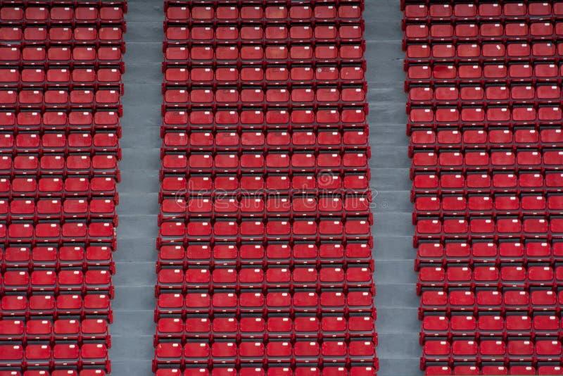 Rangées des sièges rouges vides sur l'étape du stade photographie stock libre de droits
