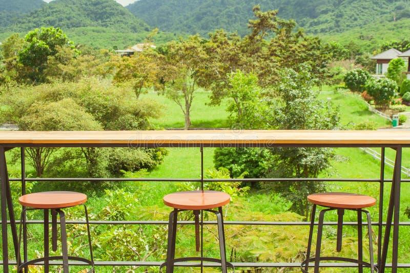 Rangées des tabourets en bois et de la contre- barre sur la terrasse extérieure avec le beau point de vue de paysage photo libre de droits
