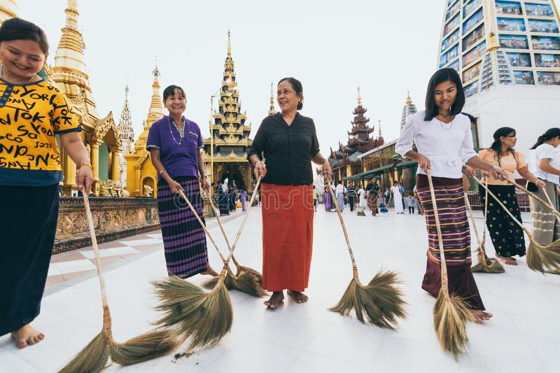 Rangún, Myanmar - marzo de 2019: Las mujeres birmanas birlan el piso en complejo budista del templo de la pagoda de Shwedagon imagen de archivo