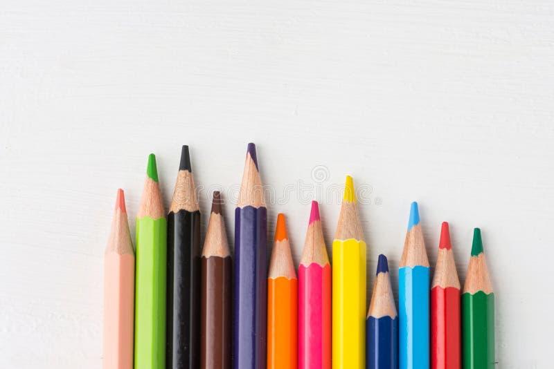 Rang?e des crayons multicolores de palette d'arc-en-ciel sur le fond en bois blanc Concept de créativité d'enfants d'éducation ar image libre de droits